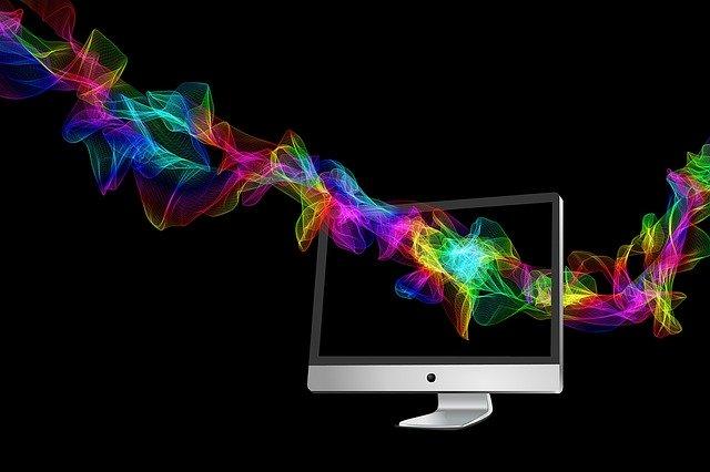 Počítač v tme cez ktorý prelieta pás plný farieb.jpg